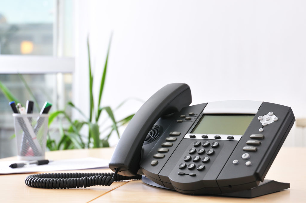 Advanced managerial VoIP phone on beech desk.